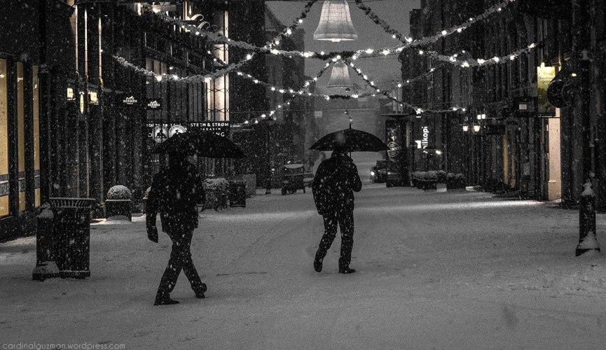 Man walking in snowfall with umbrella.